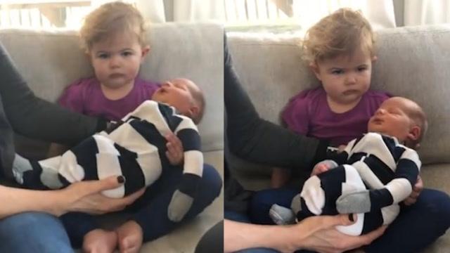 反应过于真实!小女孩怀抱新生弟弟眉头紧锁狂嘟嘴