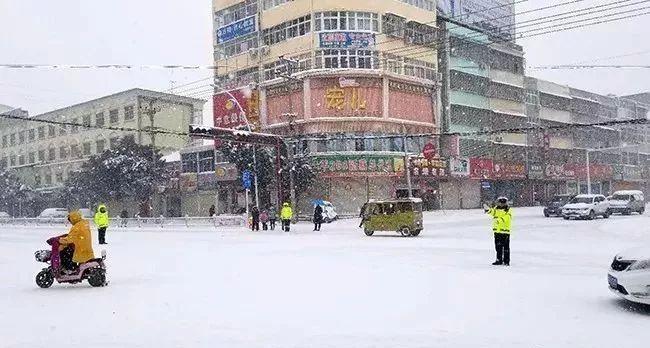 新蔡:交警在�L雪中�糖�
